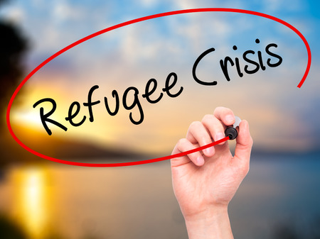 syrian civil war: Man Hand writing Refugee Crisis with black marker on visual screen. Isolated on background. Business, technology, internet concept. Stock Photo