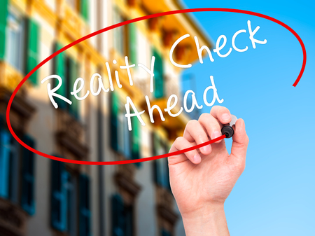 actuality: Man Hand writing Reality Check Ahead with black marker on visual screen. Isolated on city. Business, technology, internet concept. Stock Photo