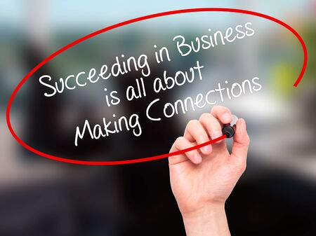 connection connections: Man Hand writing Succeeding in Business is all about Making Connections with black marker on visual screen. Isolated on office. Business, technology, internet concept. Stock Photo