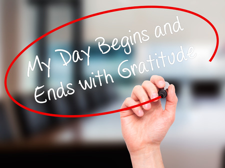 begins: Man Hand writing My Day Begins and Ends with Gratitude with black marker on visual screen. Isolated on office. Business, technology, internet concept. Stock Photo