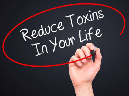 toxins: Man Hand writing Reduce Toxins In Your Life with black marker on visual screen. Isolated on black. Business, technology, internet concept. Stock Photo Stock Photo