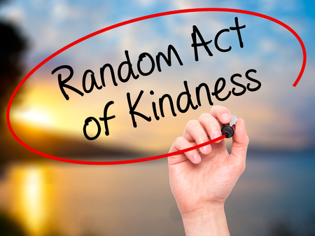 Man Hand writing Random Act of Kindness with black marker on visual screen. Isolated on nature. Business, technology, internet concept. Stock Photo