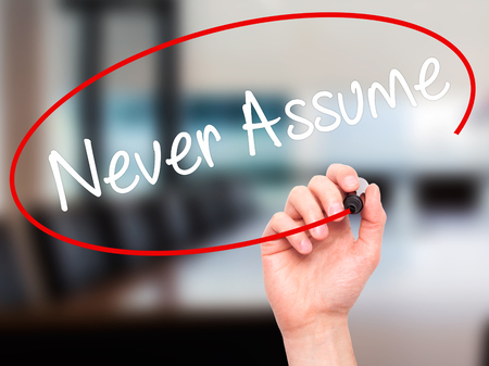theorize: Man Hand writing Never Assume with black marker on visual screen. Isolated on background. Business, technology, internet concept. Stock Photo