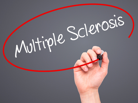 spasms: Man Hand writing Multiple Sclerosis  with black marker on visual screen. Isolated on grey. Business, technology, internet concept. Stock Photo