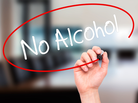 no alcohol: Man Hand writing No Alcohol with black marker on visual screen. Isolated on office. Business, technology, internet concept. Stock Photo