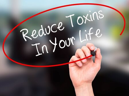 toxins: Man Hand writing Reduce Toxins In Your Life with black marker on visual screen. Isolated on office. Business, technology, internet concept. Stock Photo Stock Photo