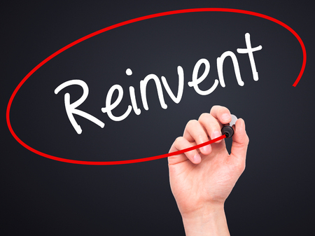 rejuvenate: Man Hand writing  Reinvent with black marker on visual screen. Isolated on background. Business, technology, internet concept. Stock Photo