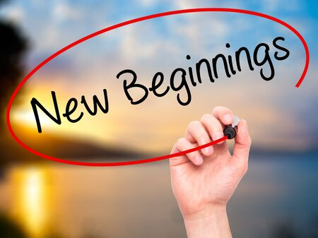 beginnings: Man Hand writing New Beginnings with black marker on visual screen. Isolated on nature. Business, technology, internet concept. Stock Photo