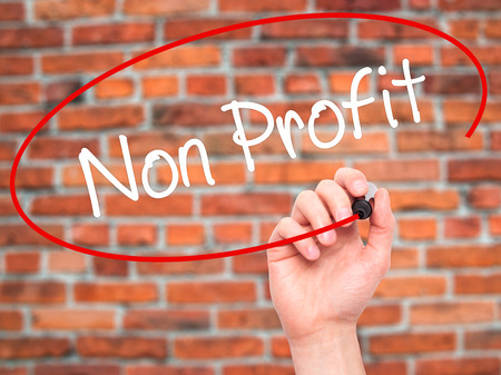 non profit: Man Hand writing Non Profit with black marker on visual screen. Isolated on bricks. Business, technology, internet concept. Stock Photo