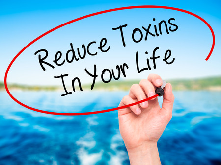 Man Hand writing Reduce Toxins In Your Life with black marker on visual screen. Isolated on nature. Business, technology, internet concept. Stock Photo