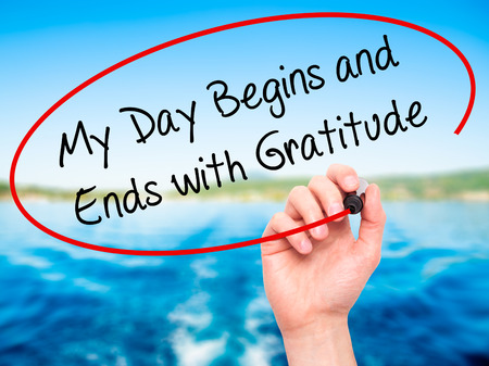 begins: Man Hand writing My Day Begins and Ends with Gratitude with black marker on visual screen. Isolated on nature. Business, technology, internet concept. Stock Photo Stock Photo