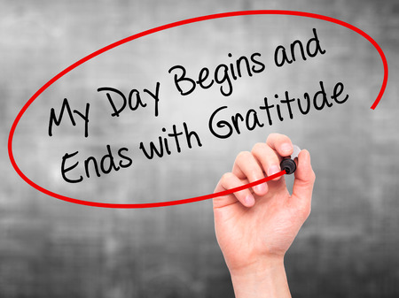 the ends: Man Hand writing My Day Begins and Ends with Gratitude with black marker on visual screen. Isolated on grey. Business, technology, internet concept. Stock Photo