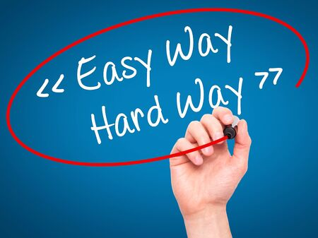 difficult lives: Man Hand writing Easy Way - Hard Way with black marker on visual screen. Isolated on background. Business, technology, internet concept. Stock Photo