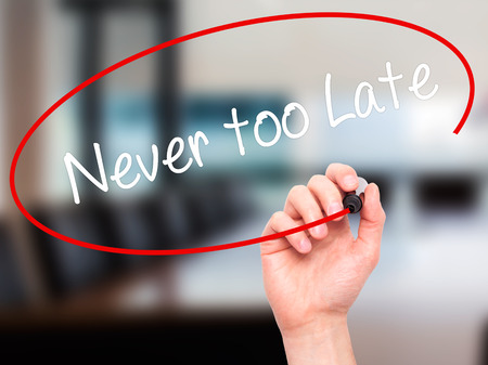 too late: Man Hand writing Never too Late with black marker on visual screen. Isolated on office. Business, technology, internet concept.