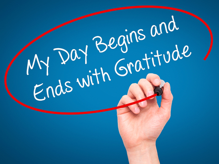 begins: Man Hand writing My Day Begins and Ends with Gratitude with black marker on visual screen. Isolated on blue. Business, technology, internet concept. Stock Photo