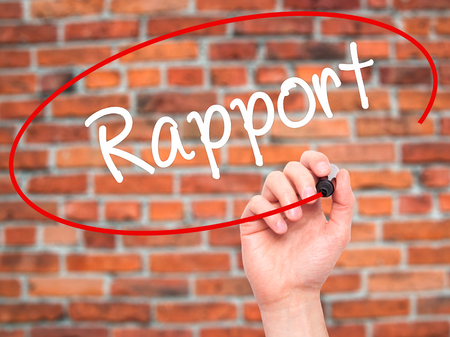 rapport: Man Hand writing Rapport with black marker on visual screen. Isolated on bricks. Business, technology, internet concept. Stock Photo
