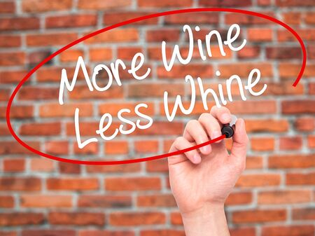 whine: Man Hand writing More Wine Less Whine with black marker on visual screen. Isolated on bricks. Business, technology, internet concept. Stock Photo