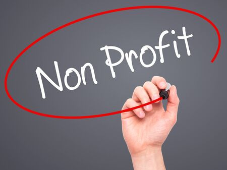 non stock: Man Hand writing Non Profit with black marker on visual screen. Isolated on grey. Business, technology, internet concept. Stock Photo