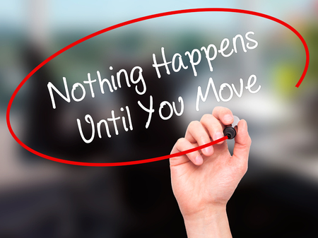 happens: Man Hand writing Nothing Happens Until You Move with black marker on visual screen. Isolated on office. Business, technology, internet concept. Stock Photo