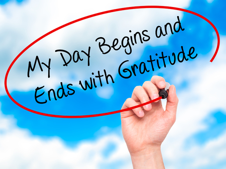 thankfulness: Man Hand writing My Day Begins and Ends with Gratitude with black marker on visual screen. Isolated on sky. Business, technology, internet concept. Stock Photo