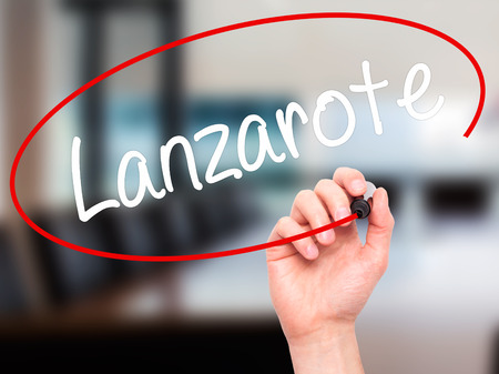 playa blanca: Man Hand writing Lanzarote with black marker on visual screen. Isolated on background. Business, technology, internet concept. Stock Photo Stock Photo