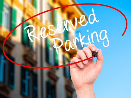 deficient: Man Hand writing Reserved Parking with black marker on visual screen. Isolated on city. Business, technology, internet concept. Stock Photo