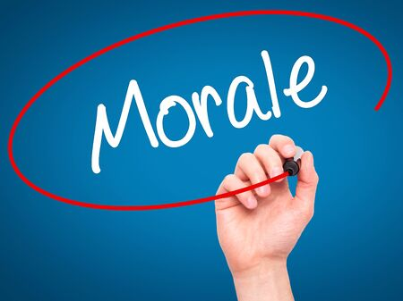 morale: Man Hand writing Morale with black marker on visual screen. Isolated on blue. Business, technology, internet concept. Stock Photo Stock Photo