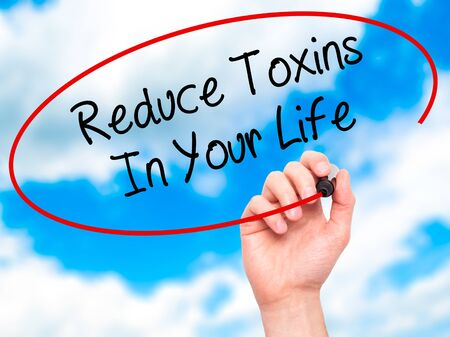 toxins: Man Hand writing Reduce Toxins In Your Life with black marker on visual screen. Isolated on sky. Business, technology, internet concept. Stock Photo
