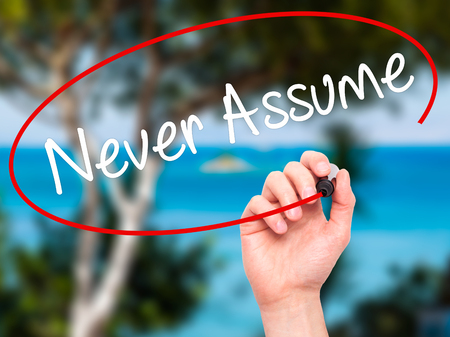 presumption: Man Hand writing Never Assume with black marker on visual screen. Isolated on background. Business, technology, internet concept. Stock Photo