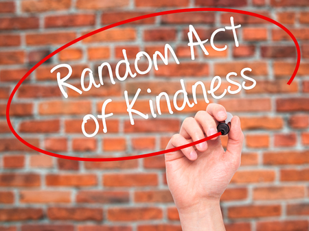 helping others: Man Hand writing Random Act of Kindness with black marker on visual screen. Isolated on bricks. Business, technology, internet concept. Stock Photo