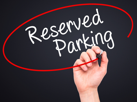 vacant sign: Man Hand writing Reserved Parking with black marker on visual screen. Isolated on black. Business, technology, internet concept. Stock Photo