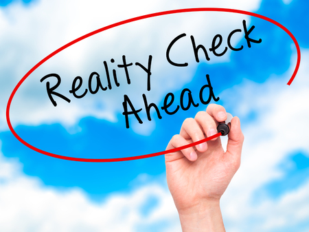 business skeptical: Man Hand writing Reality Check Ahead with black marker on visual screen. Isolated on sky. Business, technology, internet concept. Stock Photo Stock Photo