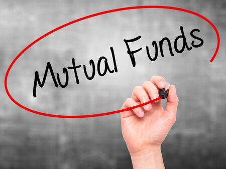 mutual funds: Man Hand writing Mutual Funds  with black marker on visual screen. Isolated on grey. Business, technology, internet concept. Stock Photo