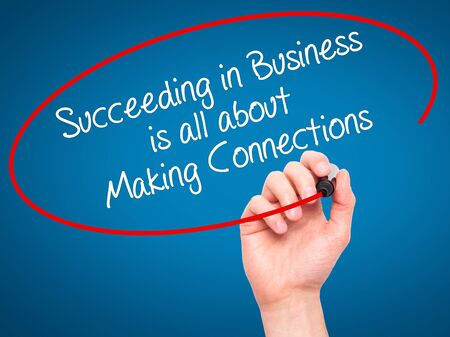 succeeding: Man Hand writing Succeeding in Business is all about Making Connections with black marker on visual screen. Isolated on blue. Business, technology, internet concept. Stock Photo