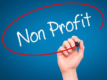 non stock: Man Hand writing Non Profit with black marker on visual screen. Isolated on blue. Business, technology, internet concept. Stock Photo