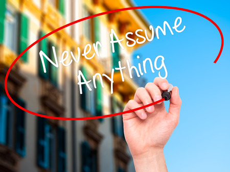 assume: Man Hand writing Never Assume Anything with black marker on visual screen. Isolated on city. Business, technology, internet concept. Stock Photo