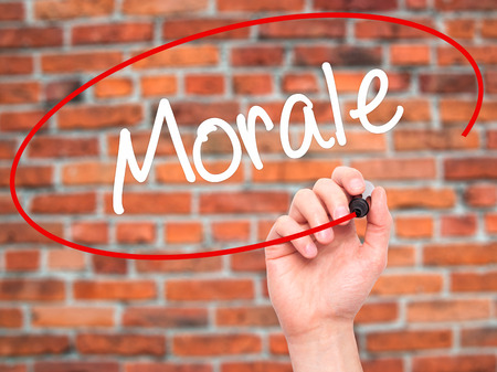 normative: Man Hand writing Morale with black marker on visual screen. Isolated on bricks. Business, technology, internet concept. Stock Photo Stock Photo