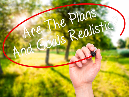 achievable: Man Hand writing Are The Plans And Goals Realistic? with black marker on visual screen. Isolated on background. Business, technology, internet concept. Stock Photo Stock Photo