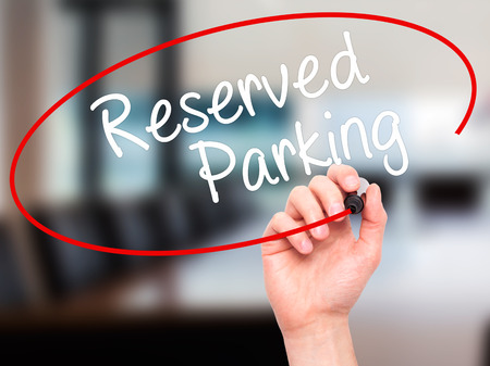 vacant sign: Man Hand writing Reserved Parking with black marker on visual screen. Isolated on office. Business, technology, internet concept. Stock Photo