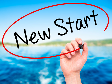 revive: Man Hand writing New Start with black marker on visual screen. Isolated on nature. Business, technology, internet concept. Stock Photo
