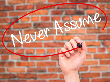assume: Man Hand writing Never Assume with black marker on visual screen. Isolated on background. Business, technology, internet concept. Stock Photo