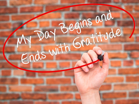 begins: Man Hand writing My Day Begins and Ends with Gratitude with black marker on visual screen. Isolated on bricks. Business, technology, internet concept. Stock Photo Stock Photo