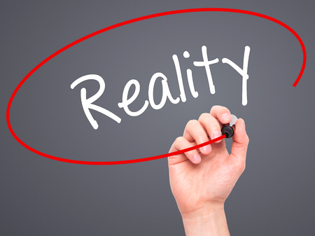 business skeptical: Man Hand writing  Reality with black marker on visual screen. Isolated on grey. Business, technology, internet concept. Stock Photo Stock Photo