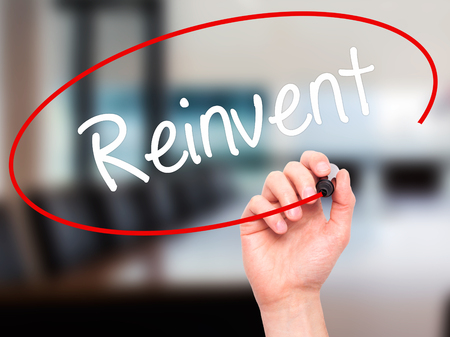 Man Hand writing  Reinvent with black marker on visual screen. Isolated on background. Business, technology, internet concept. Stock Photo