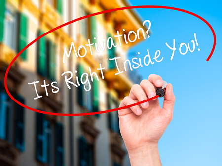 Man Hand writing Motivation? Its Right Inside You!  with black marker on visual screen. Isolated on city. Business, technology, internet concept. Stock Photo