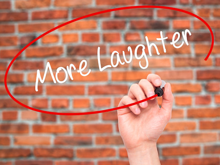 Man Hand writing More Laughter with black marker on visual screen. Isolated on bricks. Business, technology, internet concept. Stock Photo