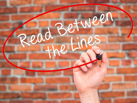 Man Hand writing Read Between the Lines   with black marker on visual screen. Isolated on bricks. Business, technology, internet concept. Stock Photo Stock Photo