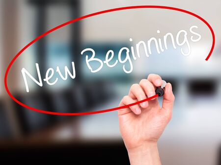 new beginnings: Man Hand writing New Beginnings with black marker on visual screen. Isolated on office. Business, technology, internet concept. Stock Photo