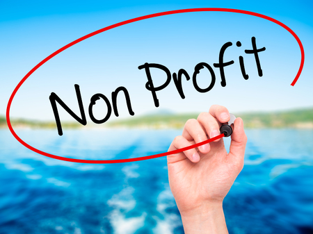 non stock: Man Hand writing Non Profit with black marker on visual screen. Isolated on nature. Business, technology, internet concept. Stock Photo