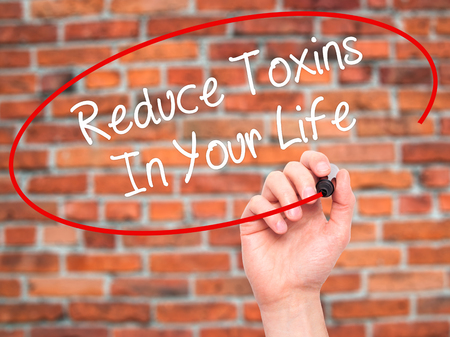 toxins: Man Hand writing Reduce Toxins In Your Life with black marker on visual screen. Isolated on bricks. Business, technology, internet concept. Stock Photo